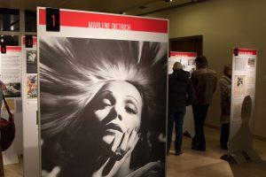 Foto zeigt eine Stele mit dem Foto Marlene Dietrich, im Hintergrund lesen Besucher Informationstafeln