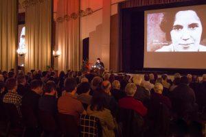 Hendrik Lietmann steht am Pult, die Gäste sitzen in der Aula und auf der Leinwand sieht man das Startbild des Films.
