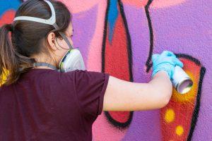Auf dem Bild sieht man ein Mädchen, das mit einer Atemmaske im Gesicht und der Sprüdose in der Hand, die Wand mit Farbe besprüht.