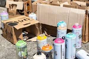 Leere Sprühdosen und Kartons, oben auf den Dosen erkennt man die Farbe, die jeweils in der Dose abgefüllt ist.