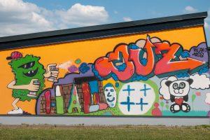 Das Bild zeigt die Wand links vom Eingang des JUZ, wo das Maskottchen mit Sprüdosen den Schriftzug JUZ oberhalb eines Pandabärs sprüht.