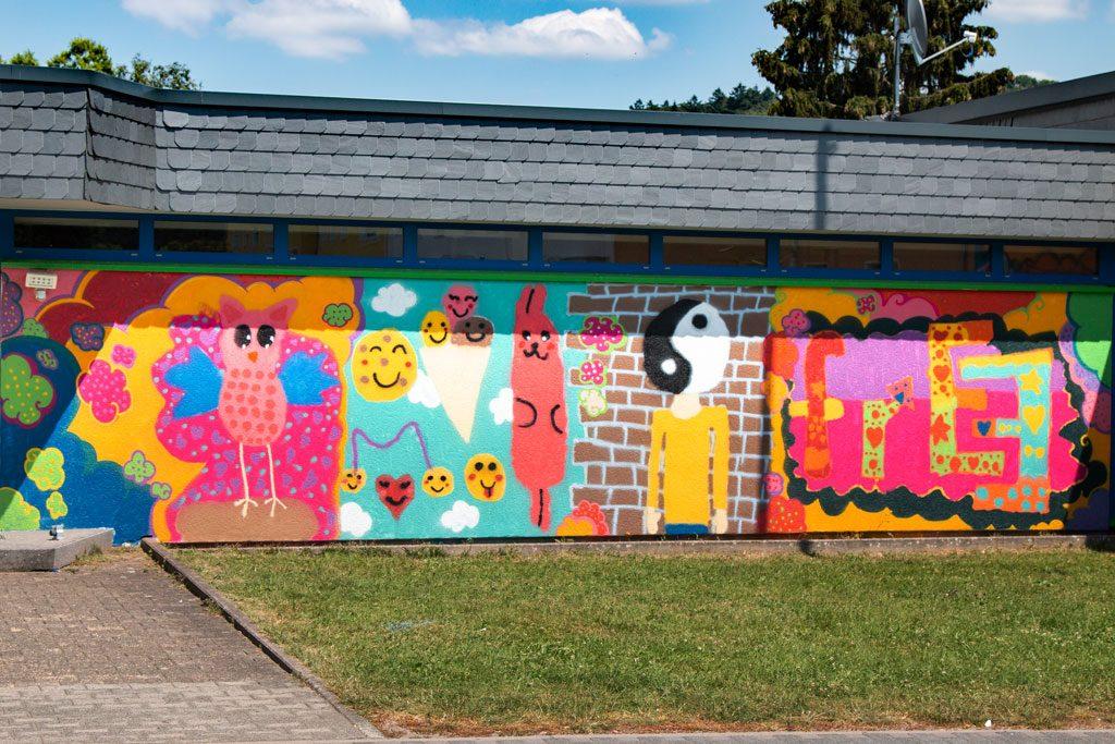 Das Bild zeigt die Wand rechts am Eingang des JUZ mit Wolken, Eule, Smilies Ying & Yang, Eis, und Hase und dem Wort: Frei