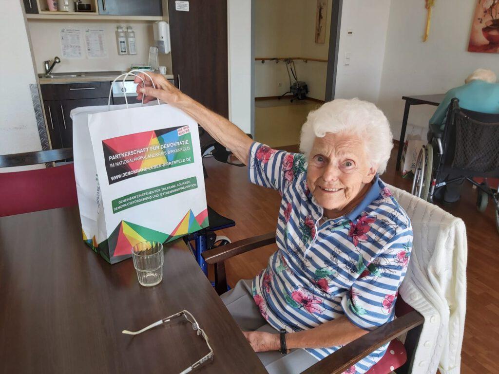 Eine Frau freut sich über die Tüte, die auf dem Tisch steht