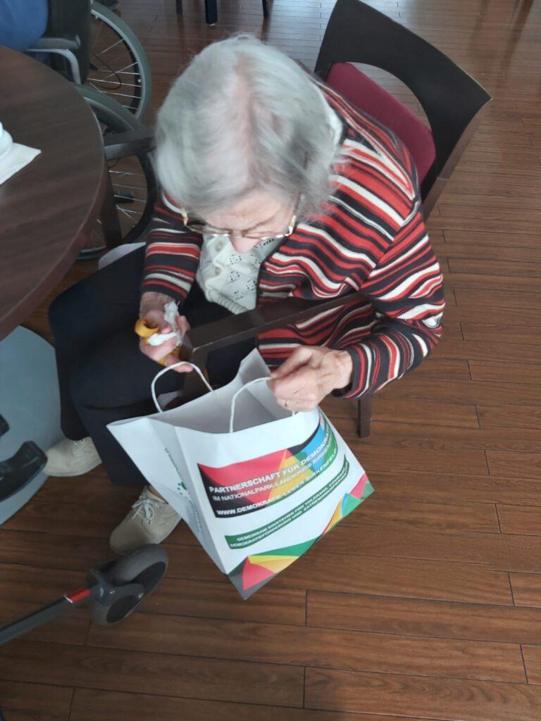 Seniorin schaut in eine geschenkte Tüte hinein