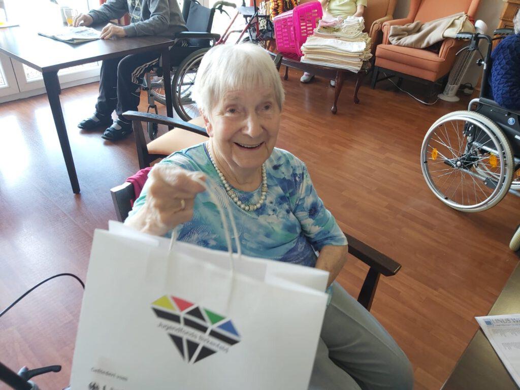eine Seniorin sitzt auf dem Stuhl und erhält eine Tüte