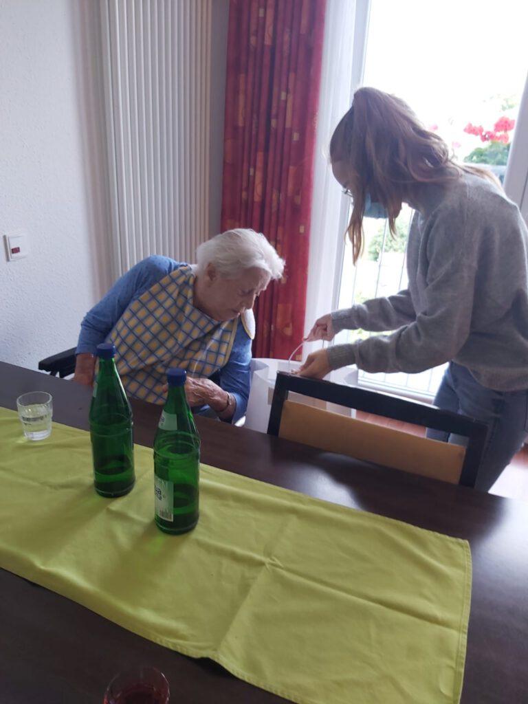 Man sieht eine junge Frau bei der Übergabe einer Tüte an eine Pensionärin