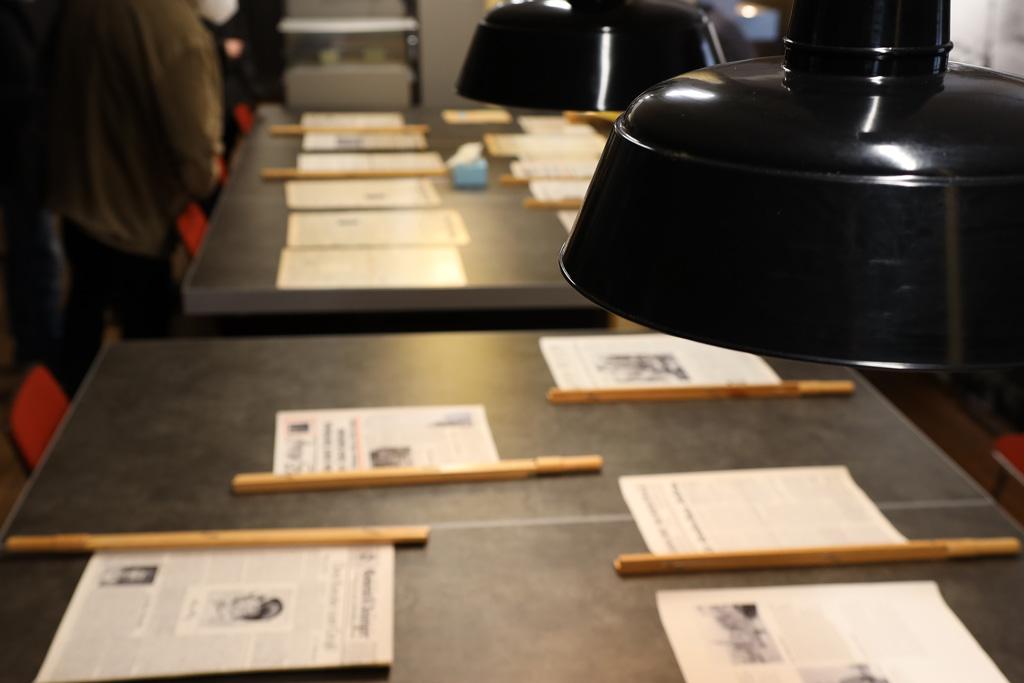 blick auf den großen Redaktionstisch mit über 12 Zeitungsseiten ausgebreitet an den tief hängenden Lampen vorbei