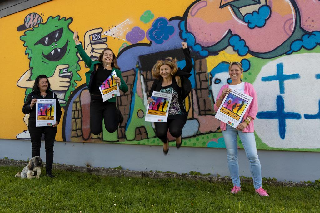 man sieht drei Frauen mit Plakaten, zwei davon springen in die Luft und alle freuen sich