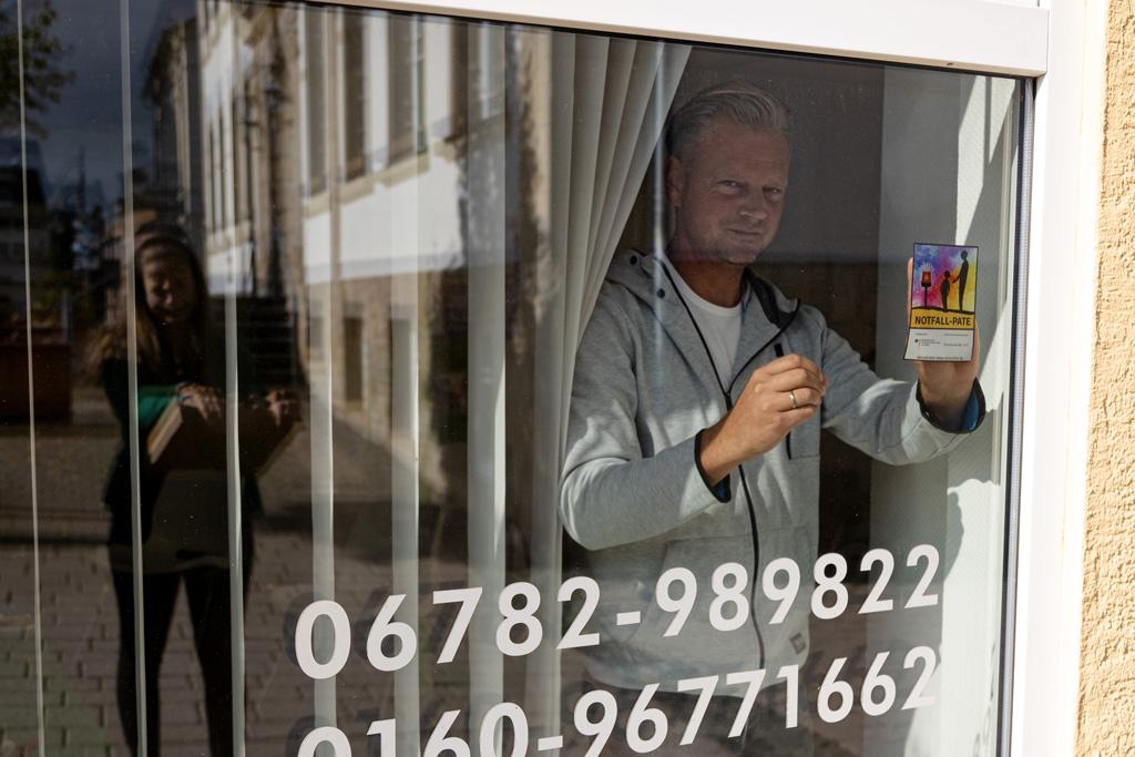Ein Mann steht im Schaufenster und bringt den Aufkleber an, darauf steht: Notfall-Pate