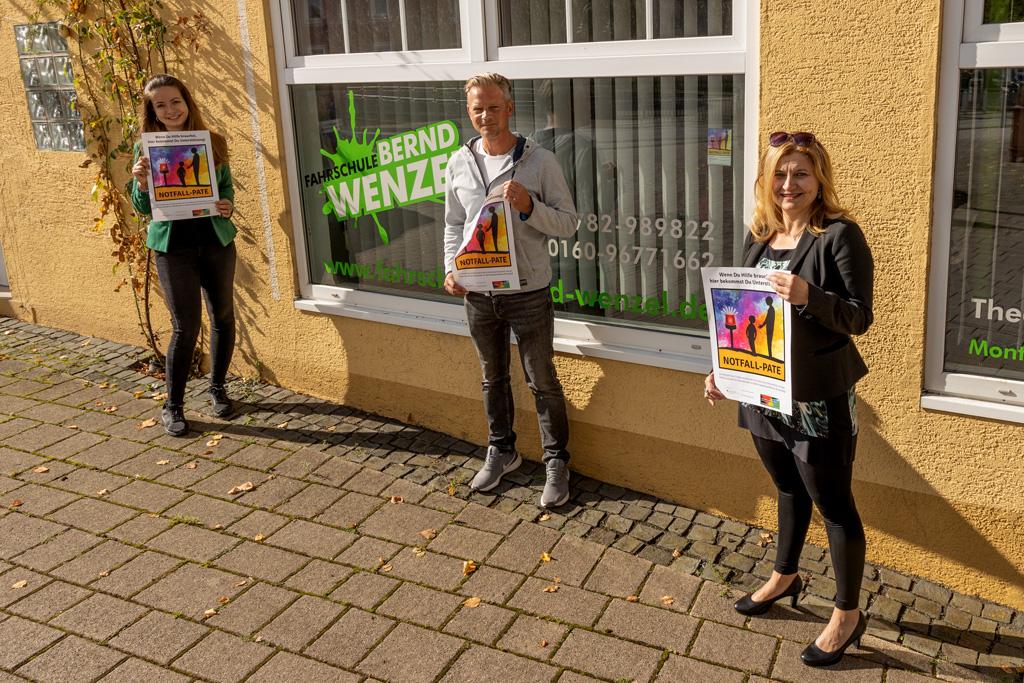 zwei Frauen und ein Mann zeigen das Plakat Notfall-Pate vor der Fahrschule Bernd Wenzel